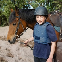 Boy with helmet and protective gear leading a brown horse