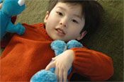Little boy with orange sweater and stuffed toy