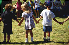 Children holding hands in a circle on the lawn