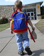 Little boy wearing a backpack heads to school, lunch in hand