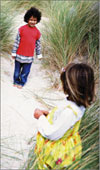 Little girl and boy on sand dunes