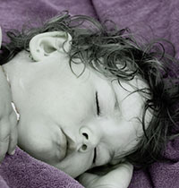 Photo of child sleeping, illustrating article on sleep-GI problems in autism