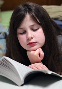 photo of girl reading book, illustrating blog about researching girls with autism