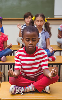 photo of boy meditating in classroom, illustrating article on treating depression in autism