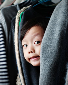 photo of boy hiding among clothes in closet