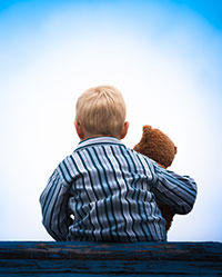 istock photo illustration of a boy in pajamas holding a stuffed animal