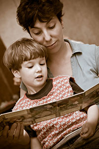 photo of mother reading bedtime story to son